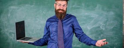 Uczyć zagadnienia używać nowożytne technologie Modnisia nauczyciel wprawiać w zakłopotanie wyrażenie trzyma laptop Dystansowej ed zdjęcia stock