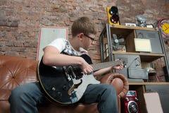 Uczy się bawić się gitarę Fotografia Royalty Free