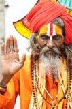 Udaipur, Индия, 14-ое сентября 2010: Святой человек в oragne одевает держать его руку вверх Стоковые Изображения RF