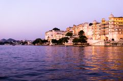 Udaipur city palace as seen form a boat on lake pichola. Udaipur city palace as seen from a boat on lake pichola at dusk with the purple gold tones. The sunset Royalty Free Stock Photos