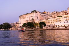Udaipur city palace as seen form a boat on lake pichola. Udaipur city palace as seen from a boat on lake pichola at dusk with the purple gold tones. The sunset Royalty Free Stock Image
