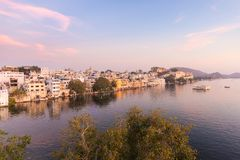 Udaipur cityscape with colorful sky at sunset. The majestic city palace on Lake Pichola, travel destination in Rajasthan, India.  Stock Photos