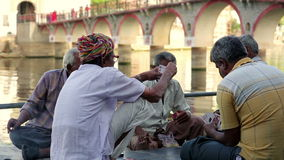 UDAIPUR, INDIA - APRIL, 2013: People playing cards by rİver stock video footage