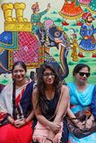 Women in front of painted wall of their house. UDAIPUR, INDIA, November 5, 2017 : Portrait of an indian family in front of her painted house in a small street of royalty free stock photography