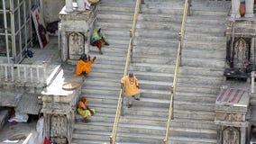 UDAIPUR, INDIEN - APRIL 2013: Leute, die auf Treppe sitzen stockbild