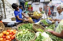 Udaipur Indien, september 12, 2010: Unga män som säljer grönsaker och frukter på en localstreet, marknadsför i Udaipur Arkivbilder