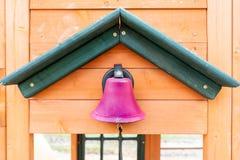 Udaje różowego szkolnego dzwon na drewnianym boisku outdoors, z sznurkiem dla robić ding Dong hałasowi, podczas gdy dzieciaki ucz obraz royalty free