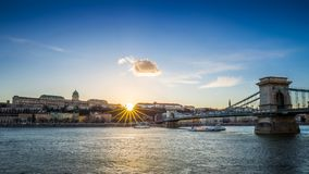 Udapest, Hungary - Sightseeing boats on River Danube at sunset with Szechenyi Chain Bridge Royalty Free Stock Images