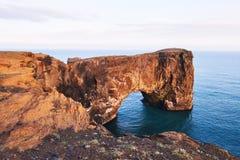 Udde Dyrholaey på sydliga Island Höjd 120 M och genomsnittlig kulleö med en dörröppning Arkivfoto