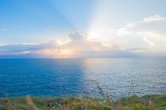 Udden av stranden med ljus solnedgång på full himmel och det härliga molnet Fotografering för Bildbyråer