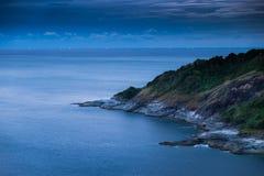 Udden av stranden på natten, havet fortfarande och ljus från fiskebåten Fotografering för Bildbyråer