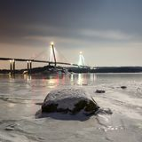 Uddevalla bridge at night during winter. Snow, ice and a rock in the foreground. Location: Uddevalla, Sweden royalty free stock images