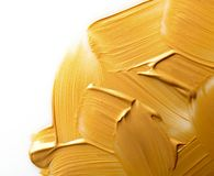 Uderzenia odizolowywający na bielu złocista farba obrazy stock