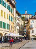 Udine, Italia: La donna in rivestimento rosso sta ciclando nel centro della città Fotografie Stock Libere da Diritti