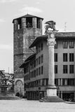 Udine - March of 2016, Italy: Old medieval tower and historical monument column Stock Photos