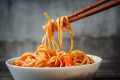 Udon лапшей взятия Hopsticks в сладостном и кислом соусе от плиты Традиционная азиатская кухня Стоковое фото RF