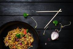 Udon beweegt gebraden gerechtnoedels met kip en groenten in wokpan op zwarte houten achtergrond met eetstokjes Hoogste mening Stock Fotografie