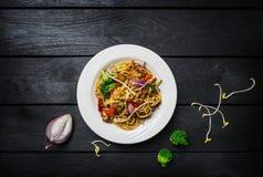 Udon fertania dłoniaka kluski z mięsem, kurczak lub warzywa w białym talerzu Zdjęcia Stock