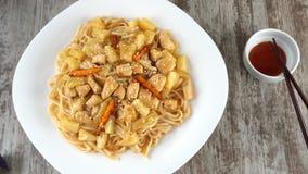 Udon-noedel met kip en groenten op een plaat stock video