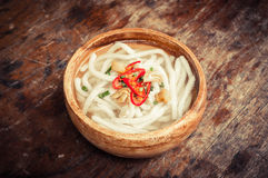 Udon noodle in wood bowl on wooden floor Stock Photo