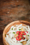 Udon noodle in wood bowl on wooden floor background Royalty Free Stock Image