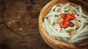 Udon noodle in wood bowl on wooden floor background Royalty Free Stock Photo