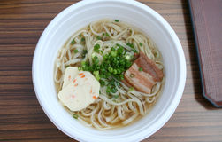 Udon noodles. A bowl of udon noodles with scallions and pork belly and fish cake Royalty Free Stock Images