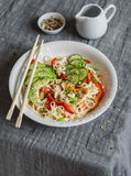 Udon noodles with quick pickled vegetables and avocado on a gray table. Healthy vegetarian food. Concept Royalty Free Stock Photography