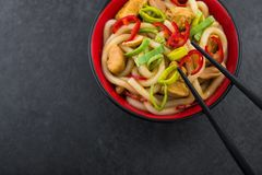 Udon noodles with red chilli pepper. And green leek in bowl. Spicy asian food Stock Images