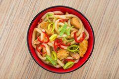 Udon noodles with red chilli pepper. On wooden table. Spicy  japanese food Stock Photography
