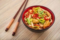 Udon noodles with red chilli pepper. On wooden table. Spicy  japanese food Stock Images
