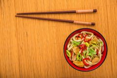 Udon noodles with red chilli pepper. On wooden table. Spicy  japanese food Royalty Free Stock Images