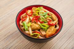 Udon noodles with red chilli pepper. On wooden table. Spicy  japanese food Royalty Free Stock Photography
