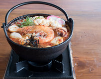 Udon in spicy Tom Yam seafood soup. A hotpot of Udon in spicy Tom Yam seafood soup Stock Photos