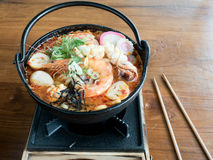 Udon in spicy Tom Yam seafood soup. A hotpot of Udon in spicy Tom Yam seafood soup Royalty Free Stock Photos