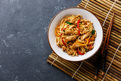 Udon stir-fry noodles with chicken in bowl. On dark stone background copy space Stock Photo