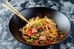 Udon stir-fry noodles with chicken meat and sesame in bowl royalty free stock image