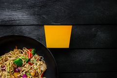Udon stir fry noodles with chicken and vegetables in wok pan on black wooden background. With a box for noodles. Stock Photos