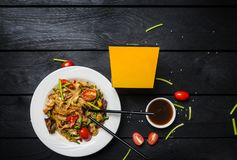 Udon stir fry noodles with seafood and mushrooms in a white plate on black background. With chopsticks and box for royalty free stock photo