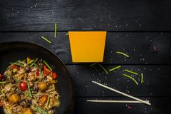 Udon stir fry noodles with seafood and vegetables in wok pan on black wooden background. With a box for noodles Royalty Free Stock Photography