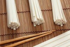 Udonnudeln und -essstäbchen auf Bambusserviette Stockbilder