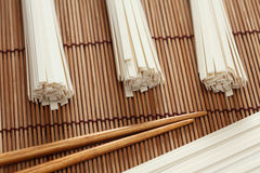 Udonnudlar och pinnar på bambuservett Arkivbilder