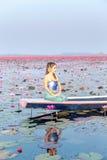 泰国传统礼服的美丽的妇女,坐在小船海上桃红色莲花在Udonthani省的 免版税库存照片