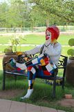 Joker sculpture is sitting on the bench. UDONTHANI, THAILAND – APRIL 22, 2018:  Joker sculpture,  be sitting on the bench,  at a garden of Thailand village Royalty Free Stock Image