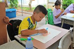 This boy is drawing a picture. UDONTHANI, THAILAND – JANUARY 12, 2018: Drawing, this boy is drawing a picture on the table, for sends it to his teacher Stock Illustration