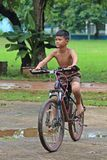 The boy rides a bicycle on the road. royalty free stock photo