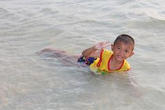He is enjoying and happy at the beach. UDONTHANI, THAILAND – JUNE 16, 2018 :  Asia boy,  he is enjoying and happy at the beach,  he likes to swim for relax Stock Photography