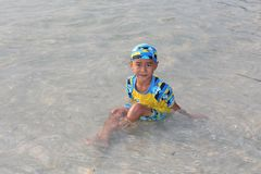 He is enjoying and happy at the beach. UDONTHANI, THAILAND – JUNE 16, 2018 :  Asia boy,  he is enjoying and happy at the beach,  he likes to swim for relax Royalty Free Stock Photos