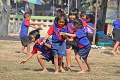 Playing to enjoy together. UDONTHANI, THAILAND – JULY 15, 2019 :  Thai student group is playing to enjoy together on the field in SPORT DAY,  see them at stock photography