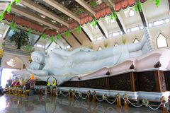 Gigantic white marble reclining Buddha In Buddhism sacred hall of Wat Pha Phu Gon temple stock photography